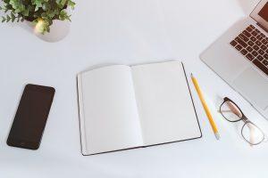 Ordinateur avec cahier de notes et téléphone portable